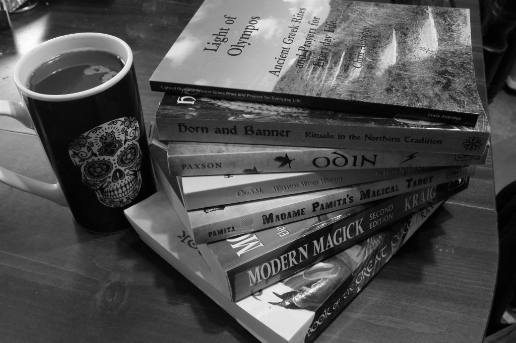 Selection of 7 Pagan books stacked next to a Coffee mug on a table.